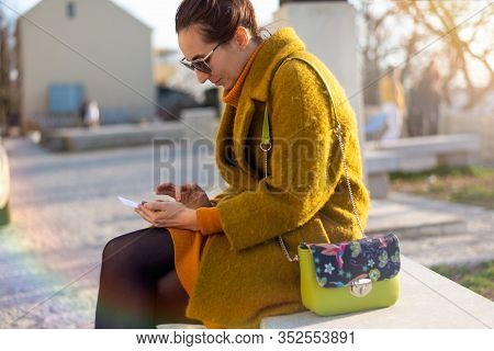 Woman Looking At Cell Phone. Woman Looking At Cell Phone While Sitting In Park. Woman Reading Messag
