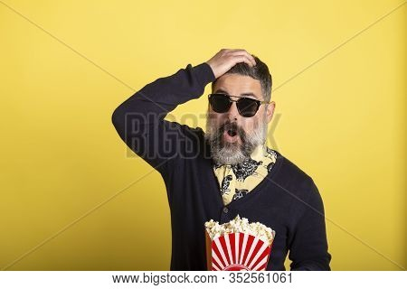 Portrait Of Handsome Man With White Beard And Sunglasses Looking Incredulously At Camera Holding A B
