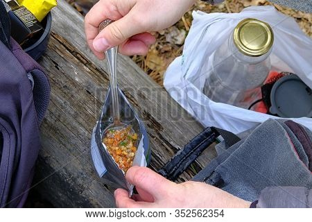 Tourist Is Eating Freeze Dried Food During Resting. Enjoy A Tasty Food During On A Hike. Food In Bag