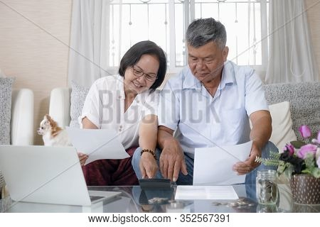 Asian Senior Couple Doing And Calculating Home Finances.