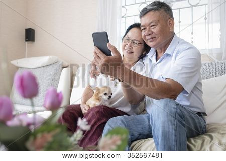 Happy Senior Couple Communicating Online With Family Via Cellphone.
