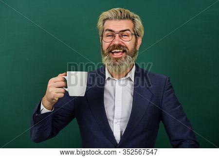 All I Need Is Caffeine. Happy Teacher Hold Coffee Cup Green Chalkboard. Enjoying Hot Caffeine Drink.