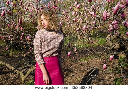 Portrait Of Blondy Beautiful Girl With Curly Long Hair. Woman Walks In The Garden Of Blooming Pink M