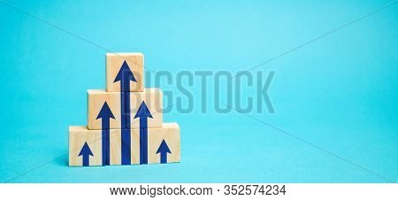 Wooden Blocks With Blue Up Arrows. The Process Of Successful Development Of Business And Economy. Pr