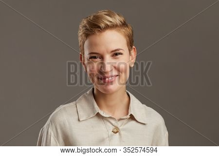 Portrait Of Smiling Young Woman With Short Pixie Haircut Looking Cheerfully At Camera While Standing