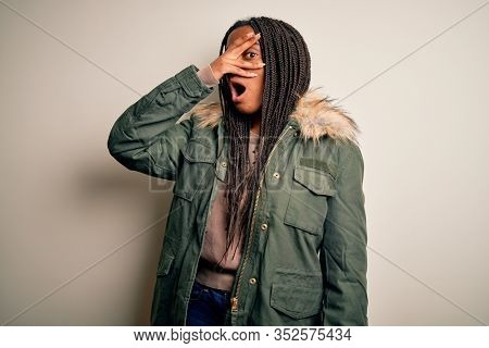 Young african american woman wearing winter parka coat over isolated background peeking in shock covering face and eyes with hand, looking through fingers with embarrassed expression.