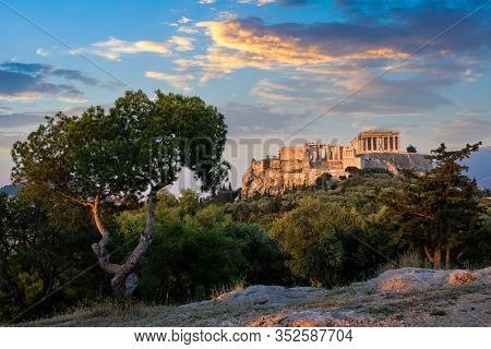 Famous greek tourist landmark - the iconic Parthenon Temple at the Acropolis of Athens as seen from Philopappos Hill on sunset. Athens, Greece