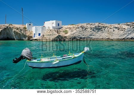Greece scenic island view - small harbor with fishing boats in crystal clear turquoise water, traditishional whitewashed house. MItakas village, Milos island, Greece.