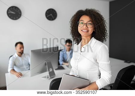 Positive Modern Female Manager In Formal White Shirt And Eyeglasses Holding Tablet And Looking At Ca