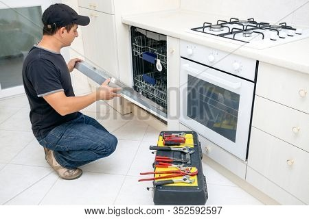 Man with tools repairing dishwasher in the kitchen