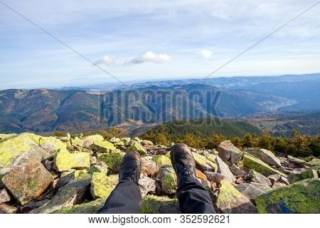 Legs of traveler sitting on a high mountain top in adventure