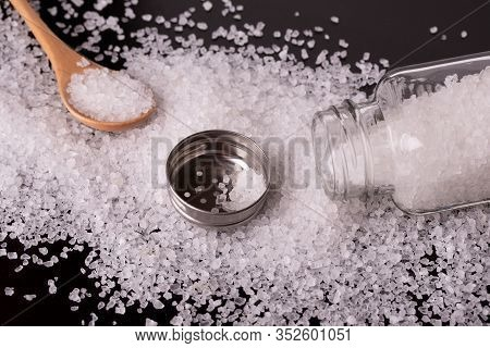 White Salt Crystals Scattered On The Table. Salt Shaker Spoon And Salt Close-up. Open Salt Shaker.