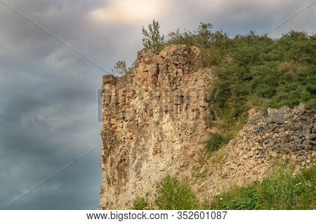 High Cliff After Mining On Dramatic Cloudy Sky Background. Exploitation Of Limestone Hills Forming U