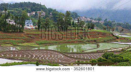 Panoramic View Of Village Of Hani People Over Terraced Rice Fields In Yuanyang, Yunnan Province Of C