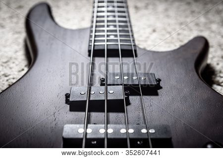 Bass Guitar With Four Strings Closeup. Detail Of Popular Rock Musical Instrument. Close View Of Dark