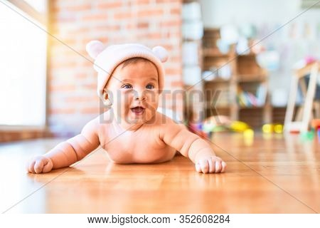 Adorable baby lying down on the sofa smiling happy at home. Newborn with smile on face wearing fanny hat relaxing and resting comfortable