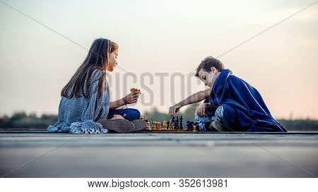 Two Young Cute Little Friends, Boy And Girl  Having Fun And Drinking Tea While Sitting By The Lake I