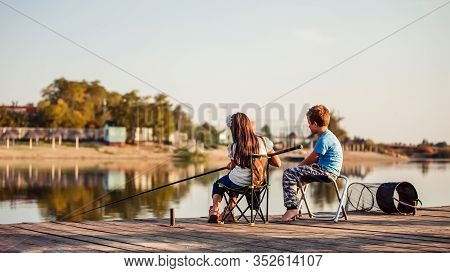 Two Cute Little Friends, Boy And Girl Fishing On A Lake In A Sunny Summer Day