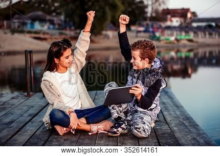 Two Cute Little Friends, Boy And Girl Having Fun Playing On Digital Tablet, Celebrating Success
