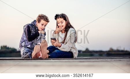 Two Cute Little Friends, Boy And Girl Watching Something On Smartphone Sitting By The Lake In The Ev
