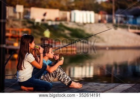 Two Happy  Little Friends, Boy And Girl Eating Sandwiches And Fishing On A Lake In A Sunny Summer Da