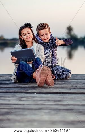 Two Happy Little Friends, Boy And Girl Having Fun Playing On Digital Tablet Outdoor