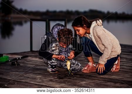 Two Young Cute Little Friends, Boy And Girl Fishing On A Lake In The Evening