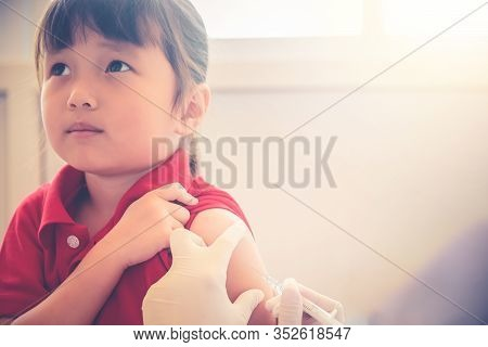 Asian Little Child Having Injection, Close-up Doctor Injecting Vaccination To Arm Of Little Girl Vac