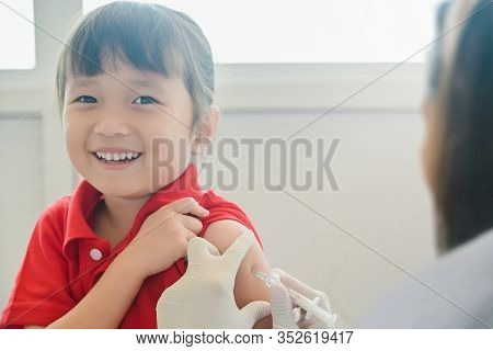 Asian Little Child Having Injection, Close-up Doctor Injecting Vaccination To Arm Of Little Girl Her