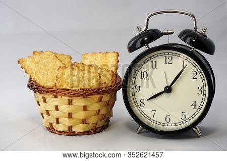 Black Classic Round Clock With Arrows And A Small Basket With Cookies. Time For A Pleasant Breakfast