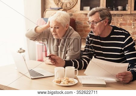 Financial Problems. Concerned Senior Couple Managing Family Budget, Using Laptop For Calculating Exp