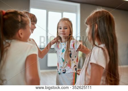 Group Of Cute And Positive Little Girls Chatting While Having A Break In The Dance Studio. Choreogra