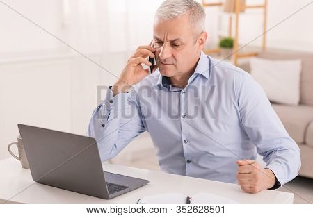 Business Calls Concept. Concerned Senior Man Talking On Mobile Phone Sitting At Desk, Looking At Lap