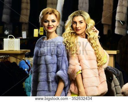 Women Buy Furry Coats. Friends In Shop: Ladies Try Overcoats