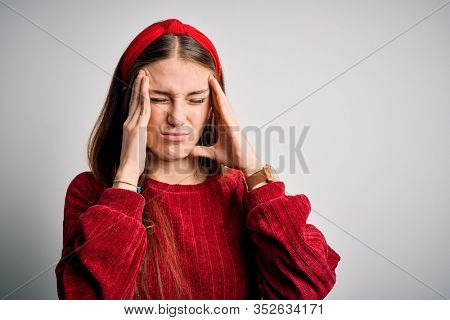 Young beautiful redhead woman wearing red casual sweater and diadem over yellow background suffering from headache desperate and stressed because pain and migraine. Hands on head.