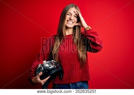 Young beautiful redhead motocyclist woman holding moto helmet over red background stressed with hand on head, shocked with shame and surprise face, angry and frustrated. Fear and upset for mistake.
