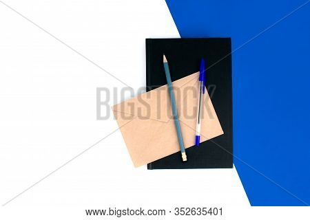 Black Notebook, Pen, Pencil, Envelope Flat Lay On White And Blue Background Top View With Copy Space