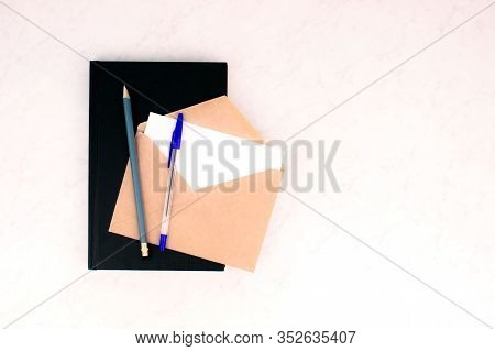 Black Notebook, Pen, Pencil, Envelope And Letter White Card Flat Lay On Marble Background Top View W