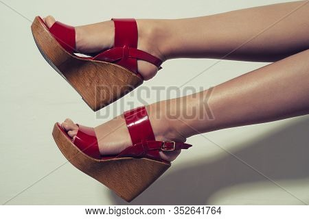 Beautiful Female Legs In Red Sandals On A Wedge On White Background