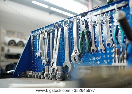 Kit of wrenches and other handtools for technical work hanging on hooks in row inside workshop of industrial plant