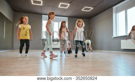 Activities For Kids. Group Of Cute And Happy Children Learning A Modern Dance In The Dance Studio. C