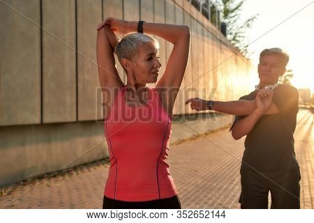 Sporty Family. Healthy And Active Middle-aged Couple In Sports Clothing Doing Stretching Exercises T