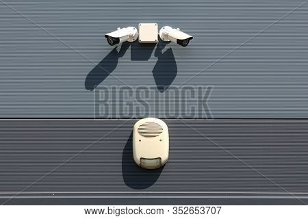 Two Small Modern White Closed Circuit Tv Cctv Security Cameras Looking In Opposite Directions Above