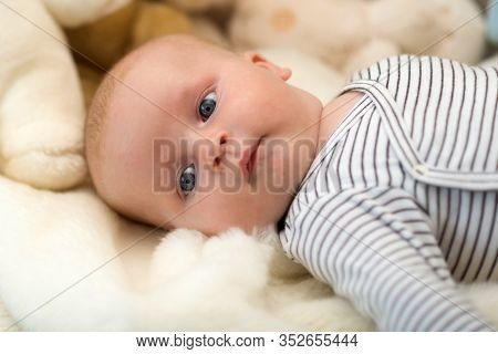 Baby Boy In Striped Bodysuit. Baby Lying On White Duvet.