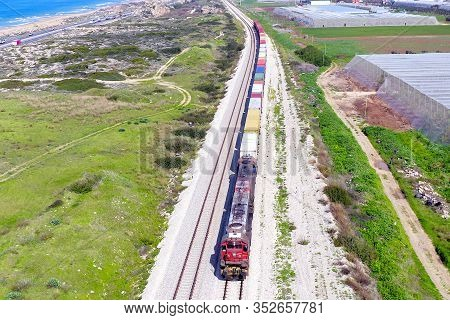 Freight Train Hauling A Long Load Of Shipping Containers.