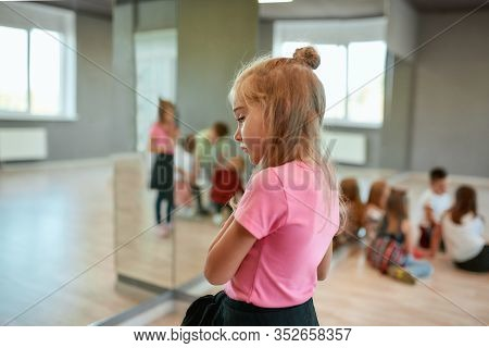 Back View Of A Little Cute Girl Looking Away And Dreaming While Standing In The Dance Studio. Group