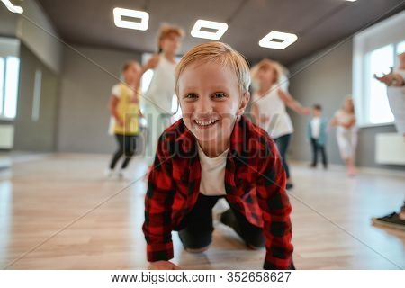 Portrait Of Funny And Cute Little Boy In Checkered Flannel Shirt Looking At Camera And Smiling While