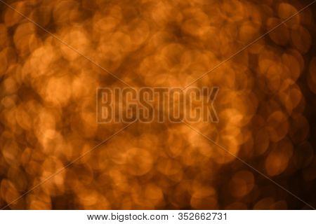 Bokeh On Gold Orange Defocused Light. Holiday Glittery Lights