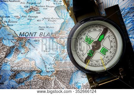 Compass on a cartographic map of the Alps.