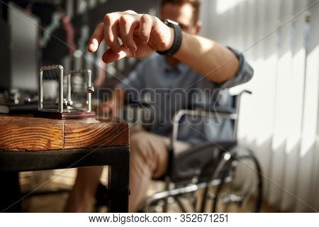 Cropped Blurred Photo Of A Businessman In A Wheelchair Moving Newton Balls While Sitting At His Work